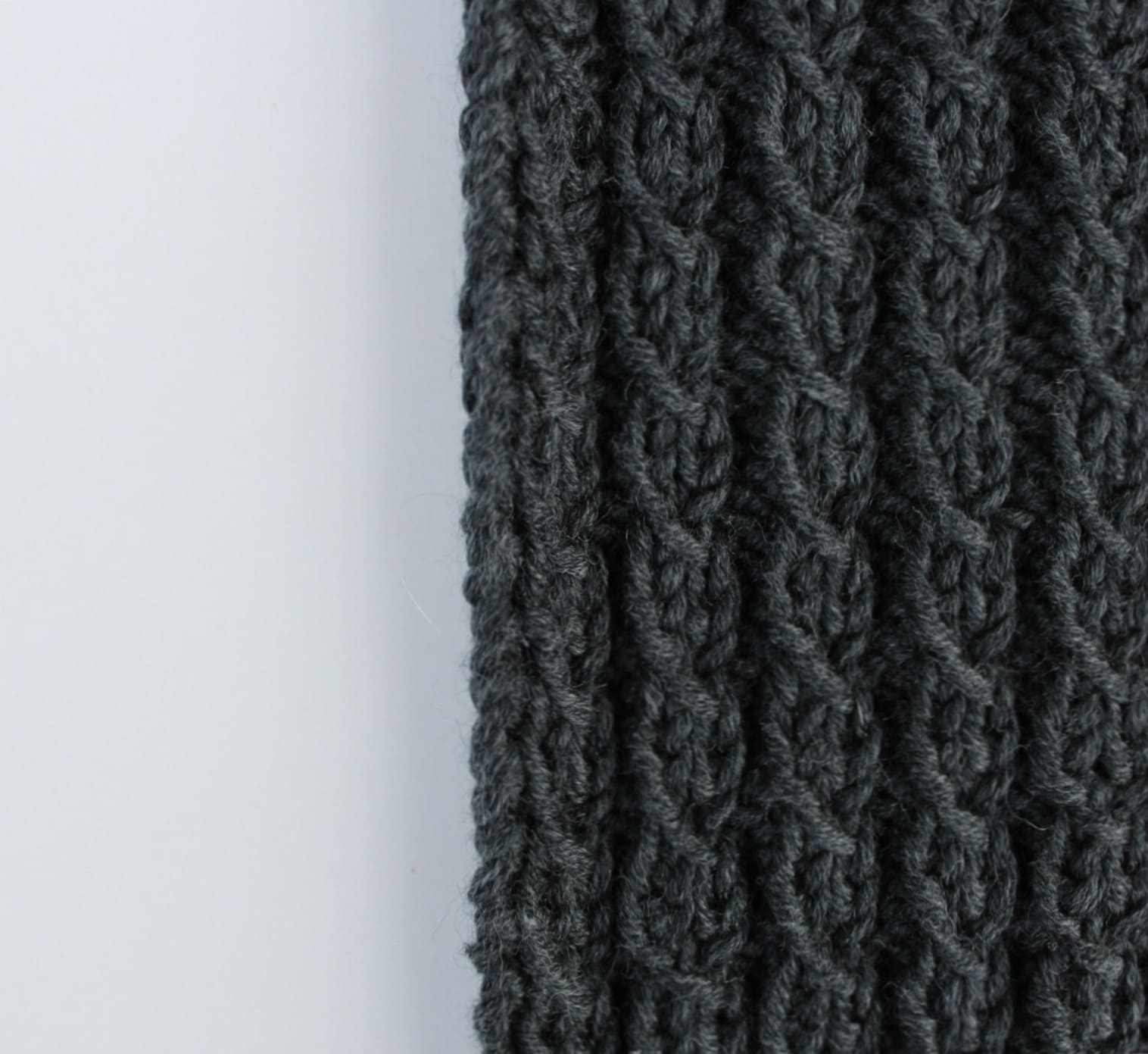 Lochmusterzöpfe stricken: Bei diesem Fantasiemuster entsteht der plastische Zopfeffekt ganz ohne zusätzliche Hilfsnadel. Die detailreiche Oberflächenstruktur auf glatt links gestricktem Grund, eignet sich besonders gut als Flächenmuster für eine Strickjacke oder einen Loop. Als einzelner Strang gefertigt, lassen sich die Lochmusterzöpfe aber auch mit klassischen Zöpfen kombinieren. Merinowolle zaubert ein schönes Maschenbild. // Strickanleitung // Strickmuster // Anthrazit // Anleitung deutsch